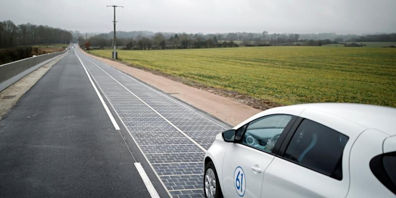 An automobile drives on a solar panel road during its inauguration in Tourouvre