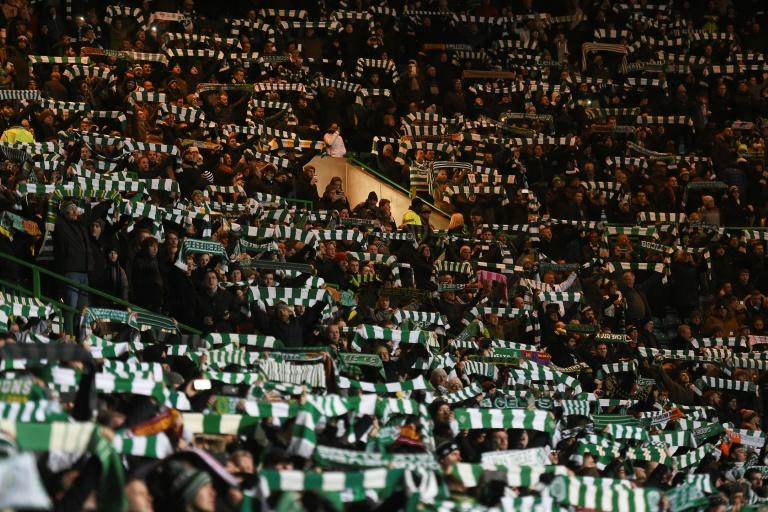 Celtic fans, whose team beat Motherwell 4-3 December 3, 2016, raise their scarves in the crowd during the UEFA Champions League group C football match between Celtic and Barcelona at Celtic Park in Glasgow on November 23, 2016