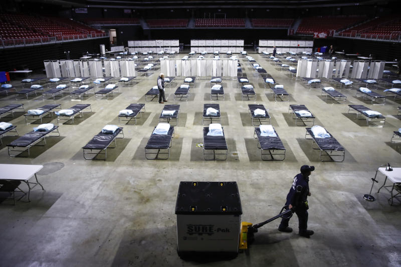 A worker moves items at a Federal Medical Station for hospital surge capacity set up at Temple University's Liacouras Center in Philadelphia, Monday, March 30, 2020. Many cities are setting up surge facilities during the coronavirus pandemic. (AP Photo/Matt Rourke)