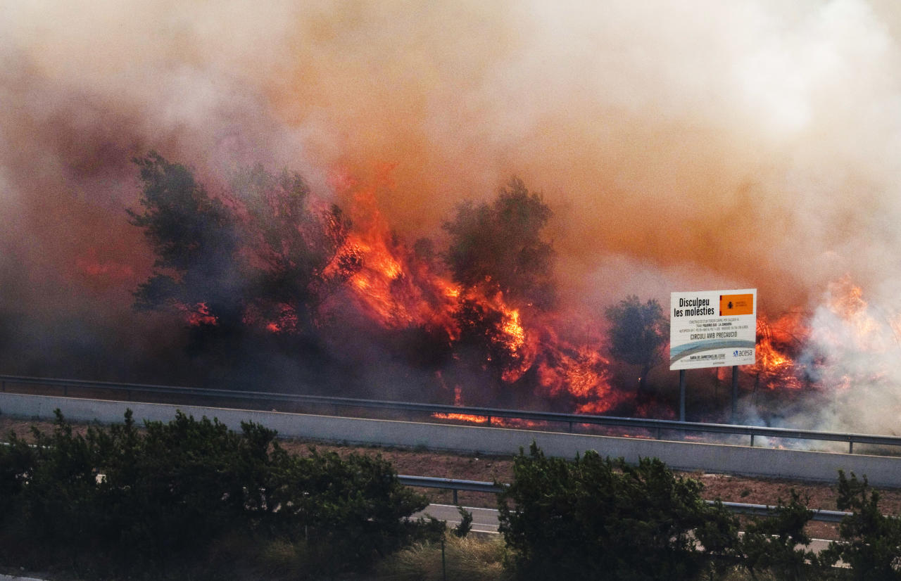 Flames ravage the forest near the highway in La Jonquera, near the border with France, Spain, Sunday, July 22, 2012. The regional officials said wildfires have burned almost 7,000 hectares (17.297 acres) of forest. Sign at right is an environmental road traffic poster. (AP Photo/Josep Rivas)