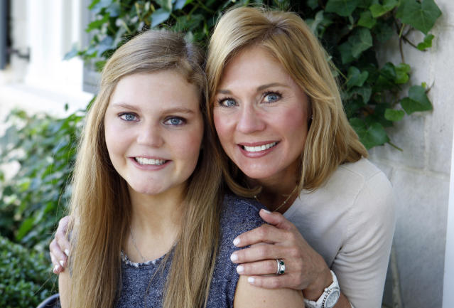 In this May 22, 2015 photo, Gracie Hussey, left, poses with her mother, Beth Hussey, at their home in Memphis, Tenn. After suffering multiple concussions playing soccer, Hussey has headaches, suffers from inexplicable nausea and several times a day she feels like she's about to pass out. While her athletic career may be over, Gracie and her mother have embarked on a new endeavor -- advocating that youth soccer coaches keep headers out of the game until kids are 14. (AP Photo/Karen Pulfer Focht)