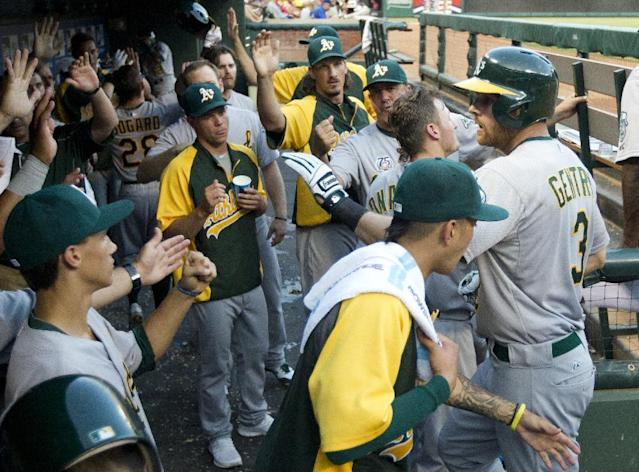 Oakland Athletics' Craig Gentry (3) and Eric Sogard (28) are greeted in the dugout after scoring on a John Jaso double in the fifth inning of a baseball game against the Texas Rangers, Sunday, July 27, 2014, in Arlington, Texas. (AP Photo/Tony Gutierrez)