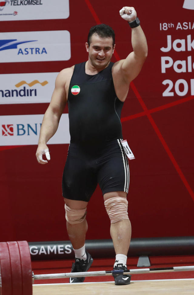 Iran's Sohrab Moradi reacts after winning gold medal during the men's 94kg weightlifting at the Asian Games in Jakarta, Indonesia, Saturday, Aug. 25, 2018. (AP Photo/Tatan Syuflana)
