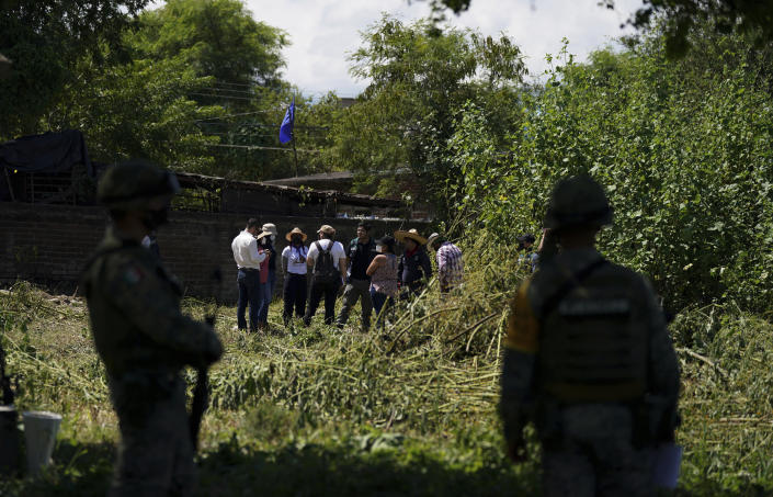 Relatives of missing people and members of the National Search Commission meet in an area where bodies are suspected to be buried, during the sixth National Search Brigade for disappeared people at a cemetery in Jojutla, Mexico, Monday, Oct. 11, 2021. The government's registry of Mexico's missing has grown more than 20% in the past year and now approaches 100,000. (AP Photo/Fernando Llano)