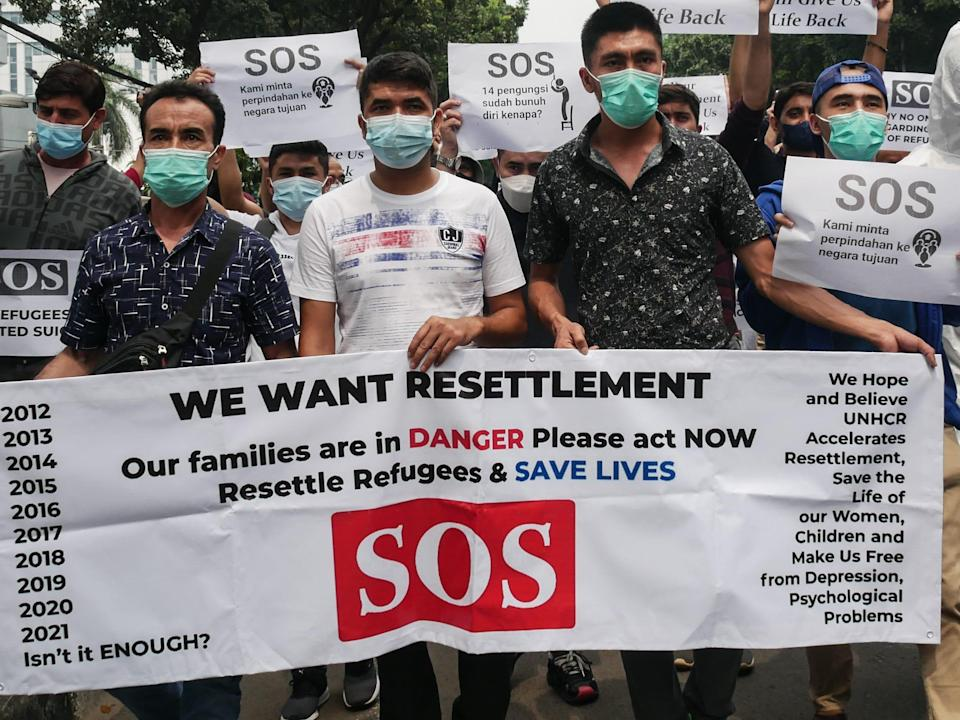 """A crowd of Afghan people with masks on hold a sign that reads: """"We want resettlement. Our families are in danger please act now. Resettle refugees and save lives. SOS"""""""