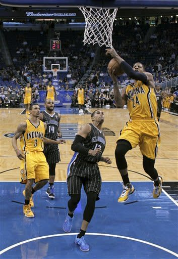 Indiana Pacers' Paul George (24) takes a shot in front of Orlando Magic's Tobias Harris, center, during the first half of an NBA basketball game, Friday, March 8, 2013, in Orlando, Fla. (AP Photo/John Raoux)