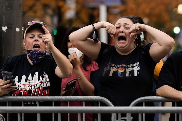 Joe Biden fans taunt Trump supporters in Washington, but the outgoing president could make moves which appeal to his base before he leaves office (AP Photo/Rebecca Blackwell)AP