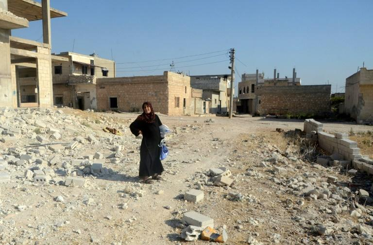 A woman stands in the ruins of Khan Sheikhun, a town almost entirely bereft of civilians after Syrian government forces took full control