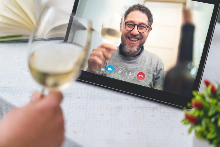 A man on a video screen raising a glass of wine.