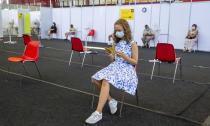 Gloria Raudjarv, 13-year-old girl, reads her vaccination certificate after getting an injection resting at a vaccination center inside a sports hall in Estonia's second largest city, Tartu, 164 km. south-east from Tallinn, Estonia, Thursday, July 29, 2021. Estonia's second largest city Tartu is making rapid progress in vaccinating children aged 12-17 ahead of the school year in September. Around half of the town's teenagers have already received their first vaccine, and local health officials are confident they will hit 70% in the coming 30 days. (AP Photo/Raul Mee)