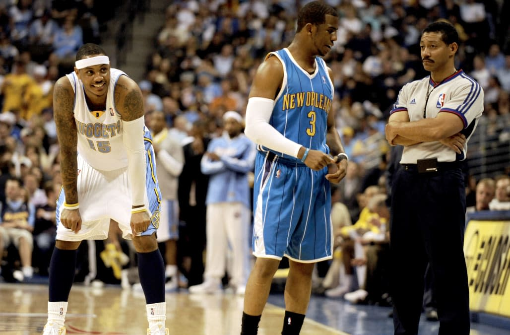 Denver Nuggets forward Carmelo Anthony (15), left, watches as New Orleans Hornets' guard Chris Paul (3),center, argues a call wi