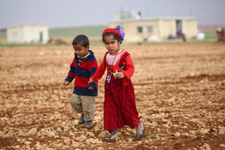 Syrian children displaced by clashes between regime forces and the Islamic State (IS) group walk in a field in Kharufiyah, 18 kilometres south of Manbij, on March 4, 2017