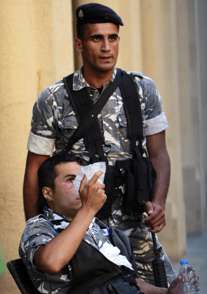 A wounded Lebanese riot police applys ice on his eye during clashes with protersters during a demonstration in Beirut, Lebanon, Thursday, June 20, 2013. Lebanon's parliament on May 29 extended its term by a year and a half, skipping scheduled elections because of the country's deteriorating security linked to the civil war next door in Syria. (AP Photo/Bilal Hussein)