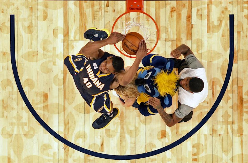 Glenn Robinson III throws down a reverse after leaping over Paul George, Pacers mascot Boomer and a Pacers dancer. (AP)