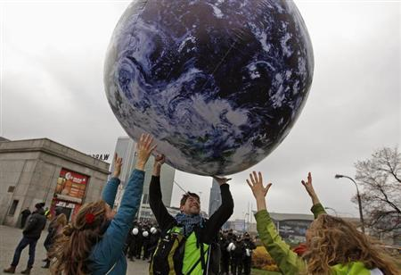 Environmental activists play with a giant globe on the streets in a rally demanding more action to battle climate change during the 19th conference of the United Nations Framework Convention on Climate Change in Warsaw