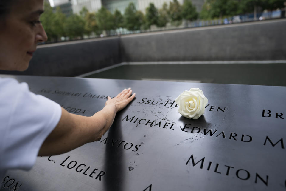 """Joan Mastropaolo, a 9/11 Tribute Museum board member, volunteer and local Battery Park city denizen since 1998, runs water over the name of Ssu-Hui Wen """"Vanessa"""", a victim of the Sept. 11 attacks, at the 9/11 Memorial & Museum, Monday, Aug. 16, 2021, in New York. Memorial personnel place flowers on the names of the deceased on their birthdays. Although Mastropaolo did not know Wen personally, she makes a point to honor memories of the fallen whenever she spots a flower. """"In many cultures, water is a symbol of life,"""" said Mastropaolo. """"I like to run water over their names on their birthdays to keep their spirit and memory alive."""" (AP Photo/John Minchillo)"""