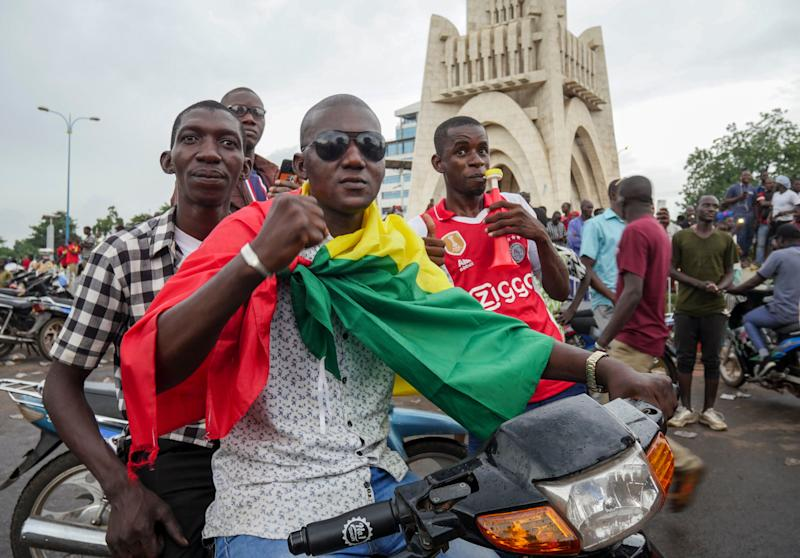 A man wears a national flag as he celebrates with others in the streets in the capital Bamako, Mali Tuesday, Aug. 18, 2020. Mutinous soldiers detained Mali's president and prime minister Tuesday after surrounding a residence and firing into the air in an apparent coup attempt after several months of demonstrations calling for President Ibrahim Boubacar Keita's ouster. (AP Photo) (Photo: ASSOCIATED PRESS)