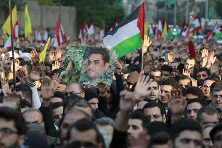 Relatives and supporters of Hezbollah militant leader Samir Qantar carry a picture of him along with Lebanese, Palestinian and Hezbollah flags during his funeral in Beirut's southern suburbs, Lebanon December 21, 2015. REUTERS/Aziz Taher
