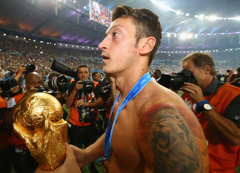 RIO DE JANEIRO, BRAZIL - JULY 13: Mesut Oezil of Germany celebrates with the World Cup trophy after defeating Argentina 1-0 in extra time during the 2014 FIFA World Cup Brazil Final match between Germany and Argentina at Maracana on July 13, 2014 in Rio de Janeiro, Brazil. (Photo by Martin Rose/Getty Images)