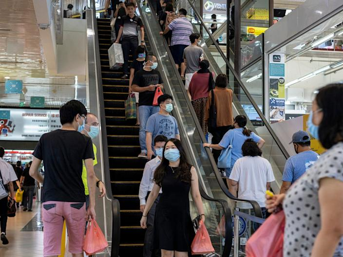 <br>People wearing protective masks stand apart from each other on the escalators in Singapore's Sim Lim Square, a popular consumer electronic mall, on April 6, 2020.