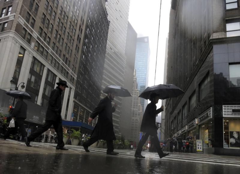 Pedestrians cross Broadway during a rain storm in New York