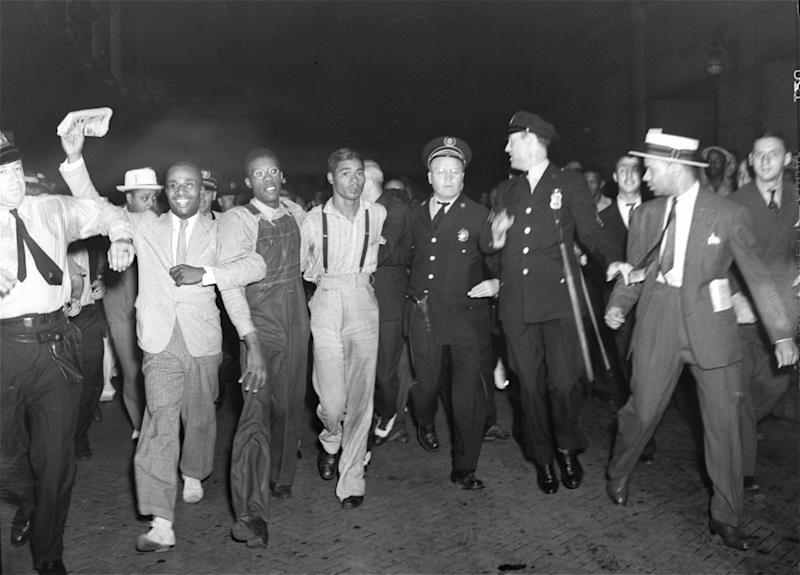 "In this July 26, 1937 file photo, police escort two of the five recently freed ""Scottsboro Boys,"" Olen Montgomery, wearing glasses, third left, and Eugene Williams, wearing suspenders, forth left through the crowd greeting them upon their arrival at Penn Station in New York. In a final chapter to one of the most important civil rights episodes in American history, Alabama lawmakers voted Thursday, April 4, 2013, to give posthumous pardons to the ""Scottsboro Boys"": nine black teens who were wrongly convicted of raping two white women in 1931. (AP Photo, File)"