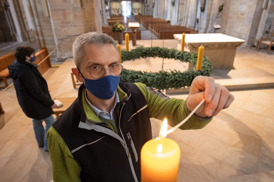 Cathedral sexton Ansgar Stuckenberg lights a candle on an Advent wreath in the Catholic St Peter's Cathedral, Lower Saxony, Osnabrück (Photo: picture alliance via Getty Images)