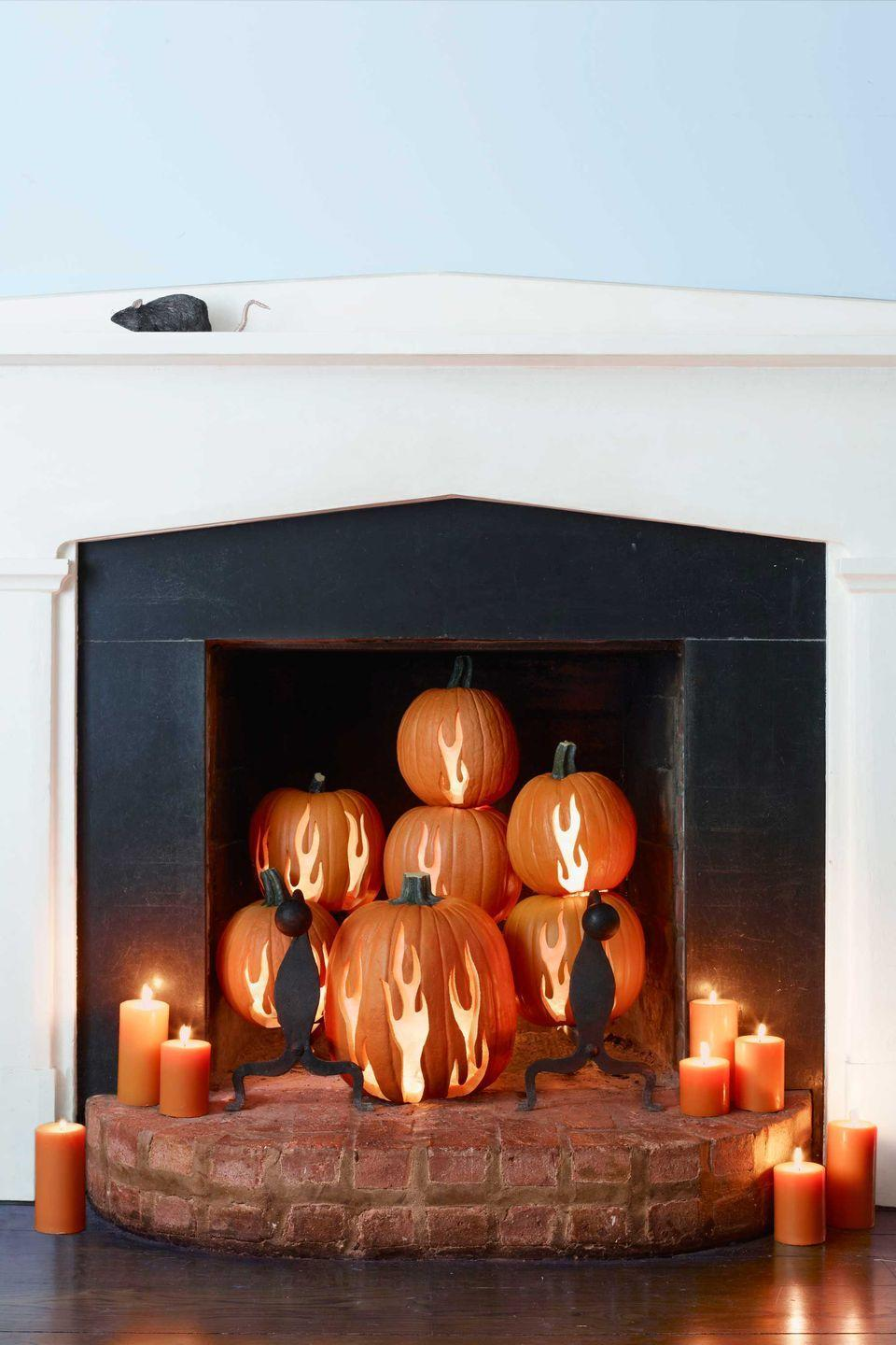 "<p>Set your hearth ablaze with these pumpkin-carved flames.</p><p><strong>Step 1:</strong> Begin by experimenting with the placement of pumpkins in your fireplace. Once you're satisfied with the arrangement, trim any stems that interfere with stacking stability, then determine how many flames each gourd should get. (Use this photo as a guide.) Note where each pumpkin goes and dismantle the arrangement.</p><p><strong>Step 2: </strong>Carve a hole in the bottom of each pumpkin, scoop out the pulp, and return the cut pieces.</p><p><strong>Step 3:</strong> Print out <a href=""https://www.countryliving.com/diy-crafts/how-to/a3048/halloween-templates-1009/"" rel=""nofollow noopener"" target=""_blank"" data-ylk=""slk:our flame templates"" class=""link rapid-noclick-resp"">our flame templates</a> and resize on a copier, scaling the images to fit your pumpkins. </p><p><strong>Step 4:</strong> Cut out stencils as directed on the templates and affix to pumpkins with masking tape. Trace on the designs with a felt-tip pen. </p><p><strong>Step 5:</strong> Remove stencils, then carefully carve along the drawn lines with an X-Acto knife. Affix a battery-operated votive candle in the base of each pumpkin with adhesive putty. Finish by restoring your arrangement. </p><p><a class=""link rapid-noclick-resp"" href=""https://www.amazon.com/Homemory-Realistic-Flickering-Flameless-Celebration/dp/B01EDKGFGU/?tag=syn-yahoo-20&ascsubtag=%5Bartid%7C10050.g.1350%5Bsrc%7Cyahoo-us"" rel=""nofollow noopener"" target=""_blank"" data-ylk=""slk:SHOP TEA LIGHTS"">SHOP TEA LIGHTS</a><br></p>"