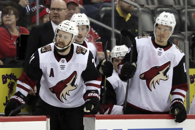 Arizona Coyotes center Derek Stepan, left, looks over at the New Jersey Devils bench during the third period of an NHL hockey game, Saturday, March 23, 2019, in Newark, N.J. The Devils on 2-1 in a shootout. (AP Photo/Julio Cortez)