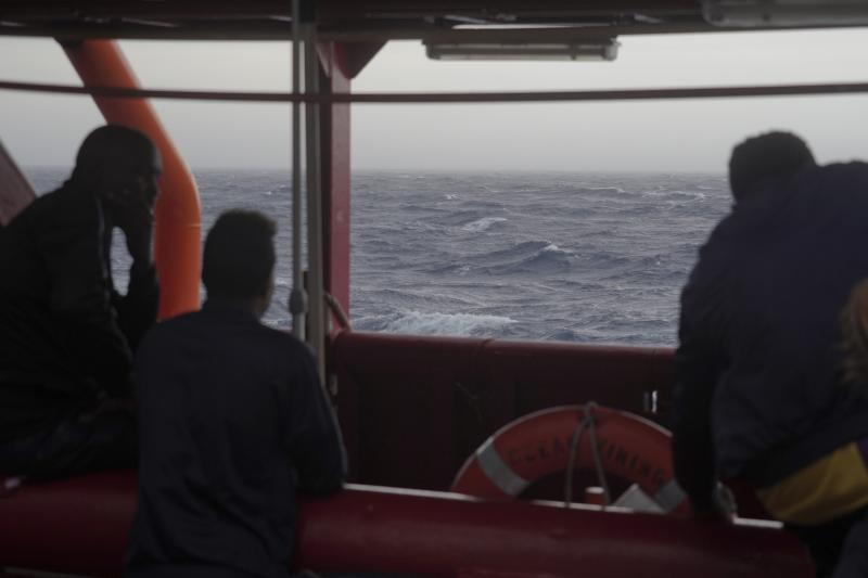 Men look at the rough seas from aboard the Ocean Viking in the Mediterranean Sea, Sunday, Sept. 22, 2019. The humanitarian ship carrying 182 people in international waters is sailing back and forth between Italy and Malta as it waits for European governments to allow it in. (AP Photo/Renata Brito)
