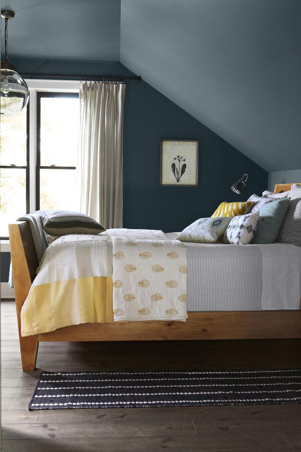 """<p>""""Dark colors make a space feel cozy, which is the ideal environment for sleep,"""" says EasyCare color expert Cynthia Cornell. """"However, be careful to only choose a bold, dark color when your bedroom has an abundant amount of natural light to balance out the cozy feeling with energy to help you wake up and start the day.""""</p><p><strong>Get the Look:</strong><br>Wall Paint Color: <a href=""""https://www.clare.com/paint/wall/irony"""" rel=""""nofollow noopener"""" target=""""_blank"""" data-ylk=""""slk:Irony by Clare"""" class=""""link rapid-noclick-resp"""">Irony by Clare</a></p>"""