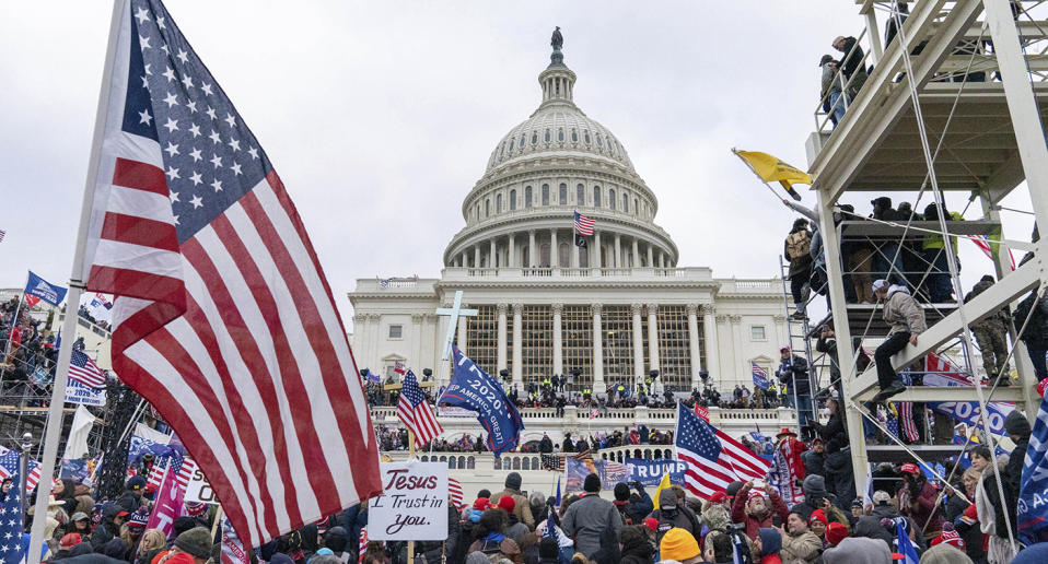 The US Capitol building in Washington DC shown surrounded by crowds carrying flags.