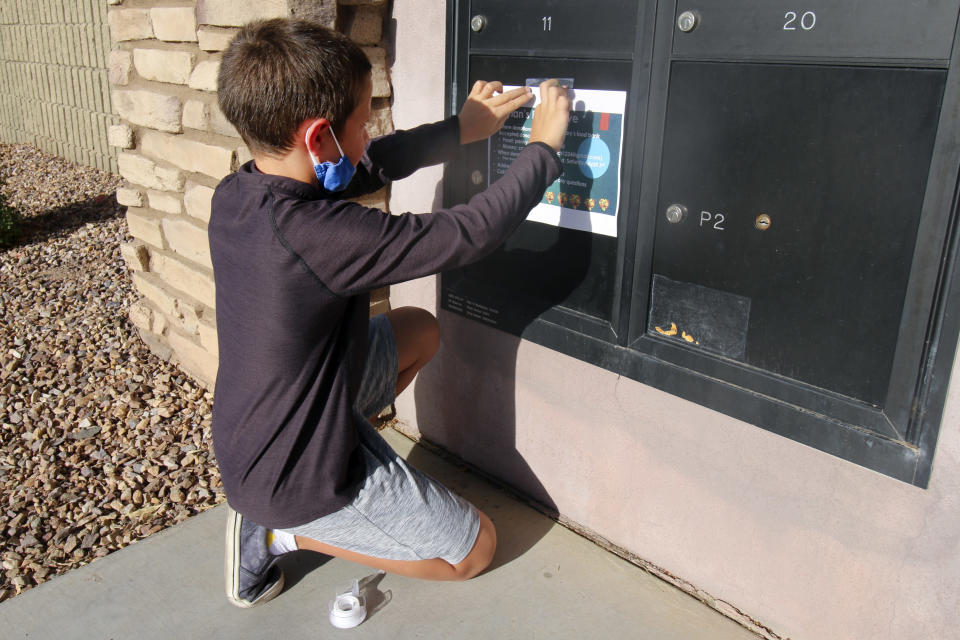 Dylan Pfeifer, 8, tapes up flyers in his neighborhood in Chandler, Ariz. on Thursday, April 1, 2021. The flyers promoted his third food drive since October in response to the coronavirus pandemic. (AP Photo/Cheyanne Mumphrey)
