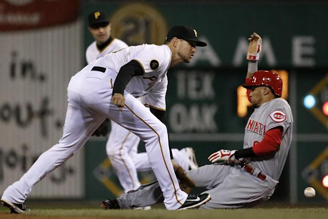 Pittsburgh Pirates shortstop Jordy Mercer (10) can't handle an errant throw from catcher Chris Stewart as Cincinnati Reds' Billy Hamilton (6) steals second during the fifth inning of a baseball game in Pittsburgh on Wednesday, April 23, 2014. Reds' Ramon Santiago scored from third on the error. (AP Photo/Gene J. Puskar)