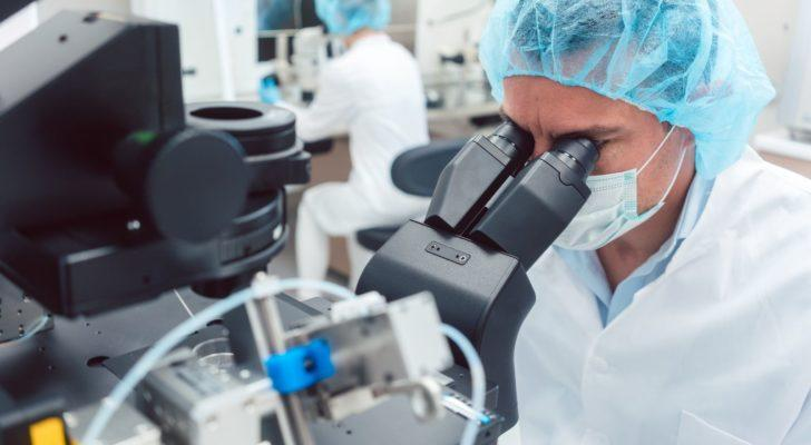 A scientist in medical gear peers through a microscope (IBIO stock)