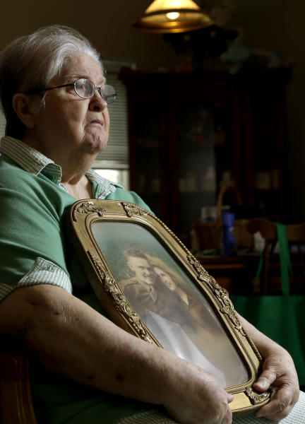 """In this photo taken Monday, July 1, 2013 in Chapel Hill, N.C., Chris Tench holds a portrait of her and her husband Kenneth F. Reese, a soldier who is still Missing In Action from the Korean War. Tench, who was later remarried, has never known what happened to Reese. The Pentagon's effort to account for tens of thousands of Americans missing in action from foreign wars is so inept, mismanaged and wasteful that it risks descending from """"dysfunction to total failure,"""" according to an internal study suppressed by military officials. (AP Photo/Gerry Broome)"""