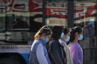 Women wearing face masks to help curb the spread of the coronavirus walk along a moving bus on a street in Beijing, Wednesday, Oct. 28, 2020. (AP Photo/Andy Wong)