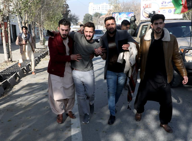 An injured man is carried as he leaves a hospital after rockets hit residential areas in Kabul