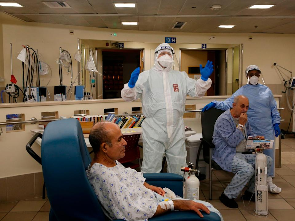 Medical staff workers at Tel Aviv's Sourasky hospital, one of hundreds of vaccination centres, bid a special farewell to a Covid patient who recovered (AFP via Getty Images)