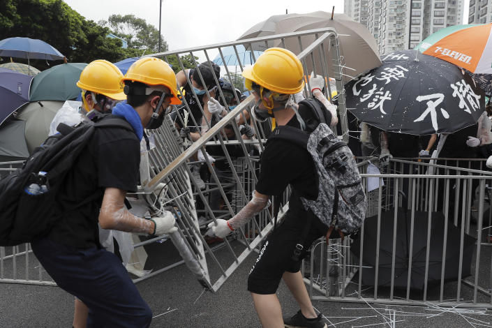 Protesters with umbrellas use steel barricades to block a road as they march through Sha Tin District in Hong Kong, Sunday, July 14, 2019. Opponents of a proposed Hong Kong extradition law have begun a protest march, adding to an outpouring of complaints the territory's pro-Beijing government is eroding its freedoms and autonomy. (AP Photo/Kin Cheung)