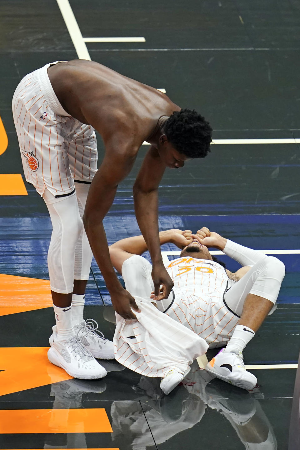 Orlando Magic center Mo Bamba, left, covers teammate guard Devin Cannady's ankle with his jersey after Cannady was injured during the first half of an NBA basketball game against the Indiana Pacers, Sunday, April 25, 2021, in Orlando, Fla. (AP Photo/John Raoux)