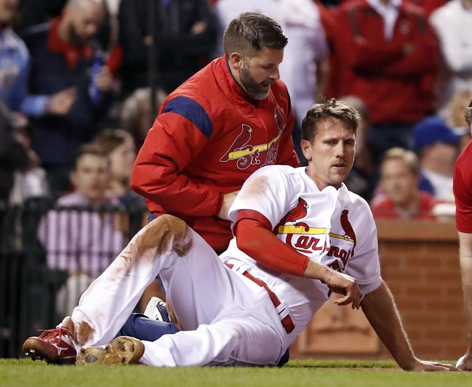 St. Louis Cardinals' Stephen Piscotty, front, is helped by a trainer after being hit in the head with a ball while scoring during the fifth inning of a baseball game against the Chicago Cubs. (AP Photo/Jeff Roberson)