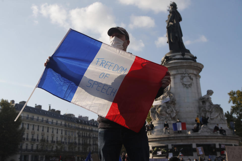 """A demonstrator holds a French flag with the slogan """"Freedom of Speech"""" during a demonstration Sunday Oct. 18, 2020 in Paris. Demonstrations around France have been called in support of freedom of speech and to pay tribute to a French history teacher who was beheaded near Paris after discussing caricatures of Islam's Prophet Muhammad with his class. Samuel Paty was beheaded on Friday by a 18-year-old Moscow-born Chechen refugee who was shot dead by police. (AP Photo/Michel Euler)"""