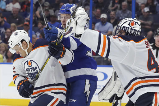 Edmonton Oilers goaltender Mike Smith reaches out to make a save as Caleb Jones defends against Tampa Bay Lightning's Yanni Gourde during the second period of an NHL hockey game Thursday, Feb. 13, 2020, in Tampa, Fla. (AP Photo/Mike Carlson)