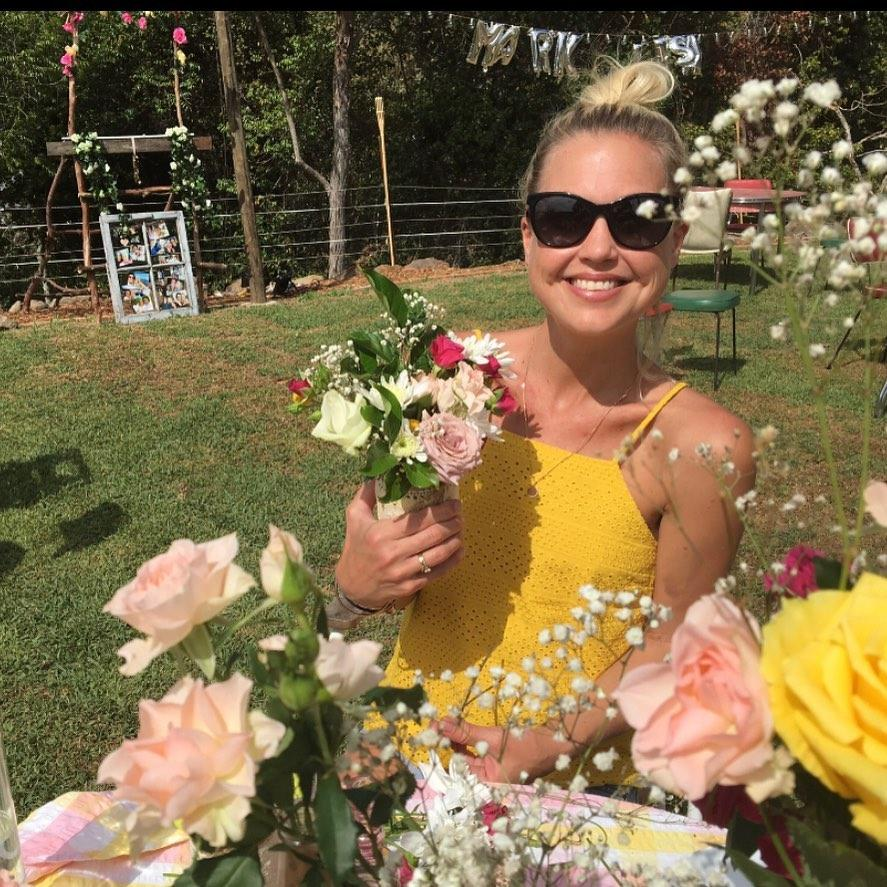 Jaimi Curry Kenny surrounded by flowers wearing a yellow dress