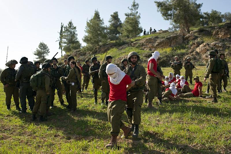 Israeli soldiers detain soldiers in red t-shirts, playing the role of Palestinian rioters, during a drill near the West Bank city of Hebron on March 1, 2015, organized by the Israeli army to simulate dispersing of riots and crowd control
