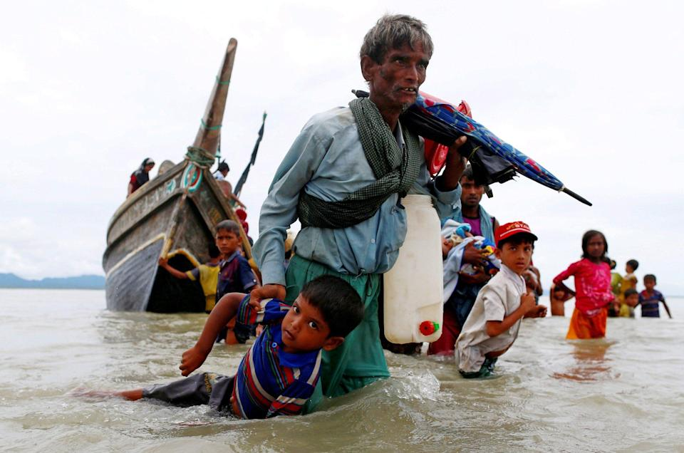 A Rohingya refugee pulls a child ashore after crossing the Bay of Bengal from Myanmar into Bangladesh in 2017 - Danish Siddiqui/Reuters