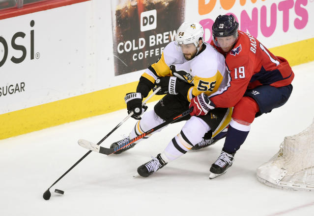 Washington Capitals center Nicklas Backstrom (19), of Sweden, holds onto Pittsburgh Penguins defenseman Kris Letang (58) during the third period in Game 2 of an NHL second-round hockey playoff series, Sunday, April 29, 2018, in Washington. (AP Photo/Nick Wass)