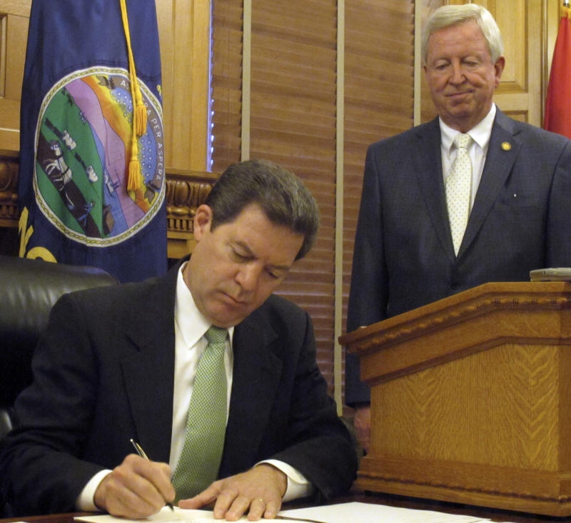Kansas Gov. Sam Brownback signs legislation attacking the long-term funding problems facing the state pension system, Wednesday, May 25, 2011, at the Statehouse in Topeka, Kan. Watching him is Senate President Steve Morris, a Hugoton Republican. (AP Photo/John Hanna)