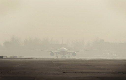 An aircraft at Beijing International Airport sits on the tarmac in heavy smog in December 2011. Beijing's government on Friday bowed to a vocal online campaign for a change in the way air quality is measured in the Chinese capital, one of the world's most polluted cities